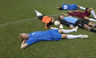 exhausted_kickers_lying_on_soccer_field_d4mo7-98